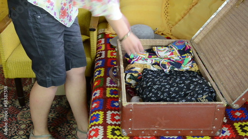 Woman unpack her clothes from old travelling port trunk bag