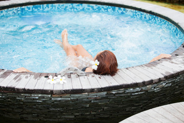 Beautiful woman relaxing in jacuzzi at spa centre