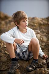 Petit garçon assis sur les rochers