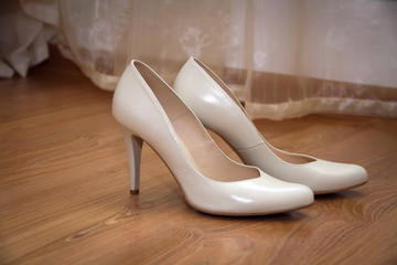 a pair of pale cream-colored wedding women's shoes
