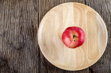 Apple in wooden dish on wooden floor