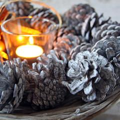 winterliche tannenzapfen mit teelicht