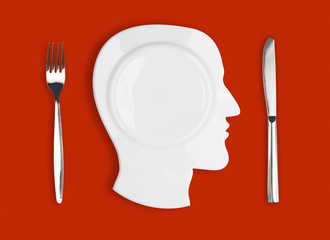 Knife, head plate and fork on red background