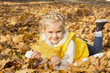 beautiful cheerful girl among autumn leaves