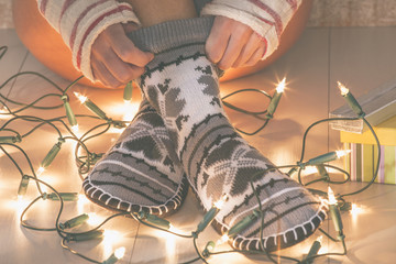 Close up of woman legs with Christmas socks, gifts and lights.