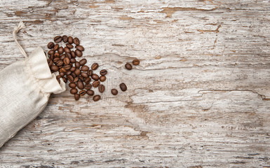 Coffee beans in a bag on the old wood