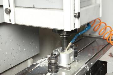 mill cutting the metal blank with cooling liquid