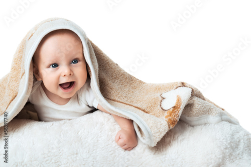 Little baby is laughing under the  carpet