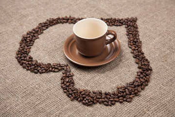 Brown cup of on burlap with coffee heart