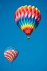 Two brightly colored hot air balloons with a sky blue background