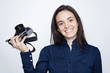 Woman photographer holding a camera over gray background
