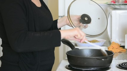 Hispanic woman cooking in her apartment