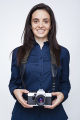Woman photographer with a camera over gray background
