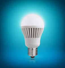 Glowing LED bulb on blue background