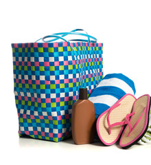 Beach bag with towel, flip-flops and suntan lotion