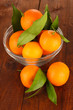Sweet tangerines with leaves, on wooden background