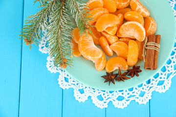 Tasty mandarine's slices on color plate on blue background