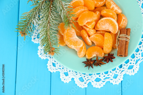 Tasty mandarine's slices on color plate on blue background