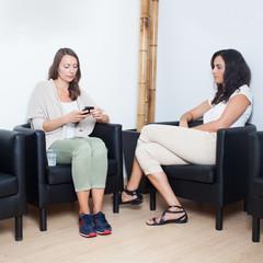Gelangweilte Frauen im Wartezimmer beim Arzt