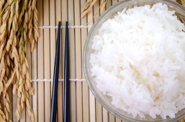 bowl of white steamed rice with chopsticks on bamboo mat.