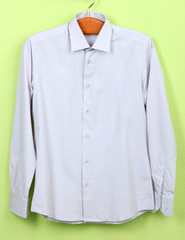 Male shirt on wooden hanger on wall background