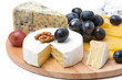 Assorted cheeses and grapes on a wooden board, isolated