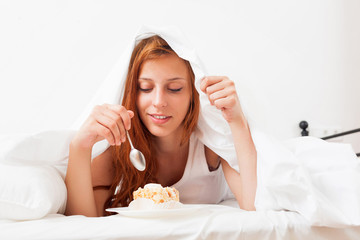 woman eating sweet cake  in bed