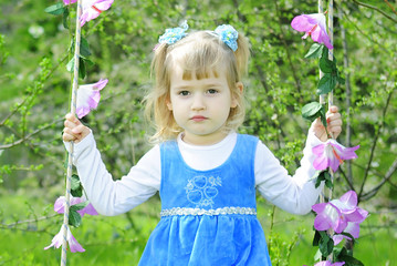 little girl on green grass in the spring in a Blue Dress