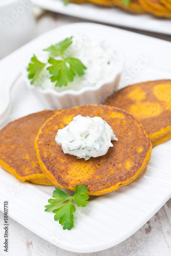 Pumpkin fritters with fresh herbs and feta sauce, close-up