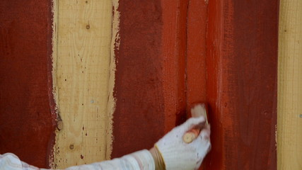 hand paint outdoor wood plank wall with brush in red color