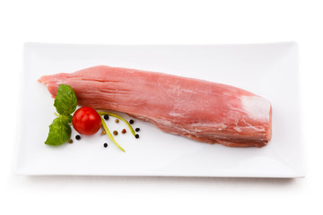 Raw pork loin and vegetables on white background