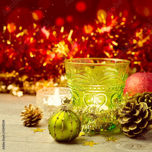 Candle glass with Christmas ornaments over bokeh background