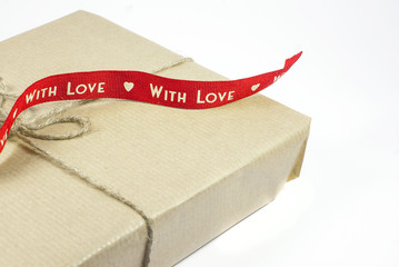 """Gift box with red ribbon """"With love"""" on a white background"""