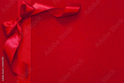 Christmas ribbon with bow on red fabric background