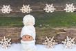 Wichtel im Schnee vor Holz