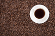 White cup with coffee on coffee beans
