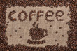 Cup shaped scattered coffee beans on burlap