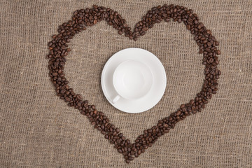 White cup of on burlap with coffee heart top