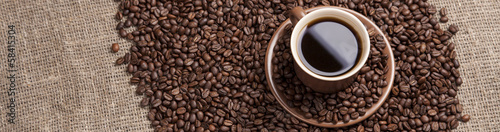 Brown cup with coffee on coffee beans