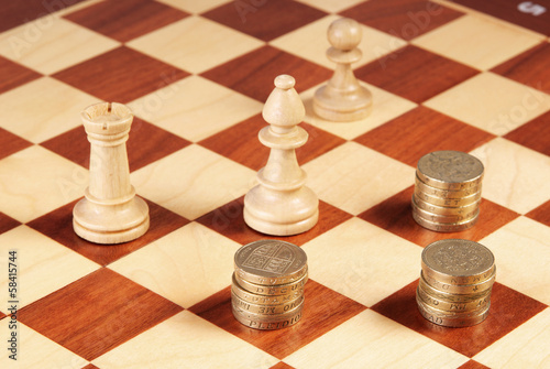 Chess board with coins and chess pieces