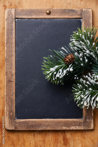 Vintage slate chalk board with Fir branch on wooden background
