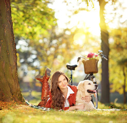 Beautiful female lying on grass with her dog in a park