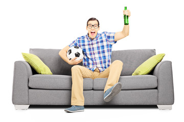 Excited male sport fan with ball and beer watching sport