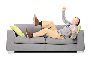 Excited senior male seated on a sofa listening music