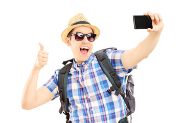Male tourist taking pictures of himselves and giving thumb up
