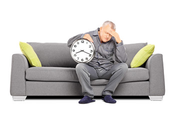 Mature man in pajamas holding a clock and having a headache