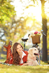 Beautiful female on grass with her labrador retriever dog in a p