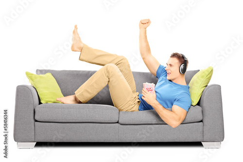 Excited guy lying on a sofa and listening music