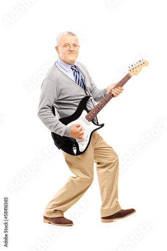 Full length portrait of a smiling senior man playing guitar