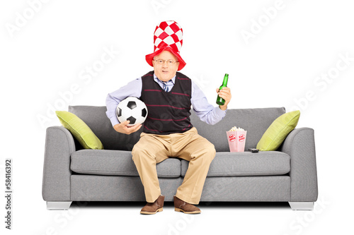 Mature sport fan holding a ball and beer watching sport